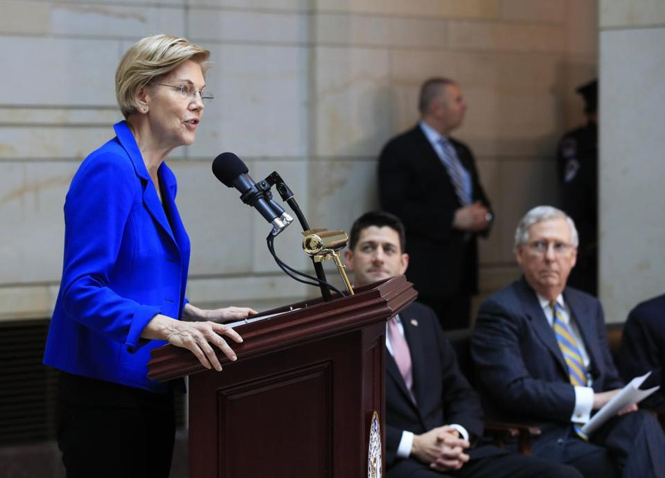 Sen. Elizabeth Warren, D-Mass., from left, speaks, while House Speaker Paul Ryan of Wis., and Senate Majority Leader Mitch McConnell of Ky., listen during a ceremony in the U.S. Capitol's Emancipation Hall in Washington, Wednesday, Nov. 8, 2017, dedicating and unveiling the commemorative chair in honor of U.S. prisoners of war and the service members missing in action. (AP Photo/Manuel Balce Ceneta)