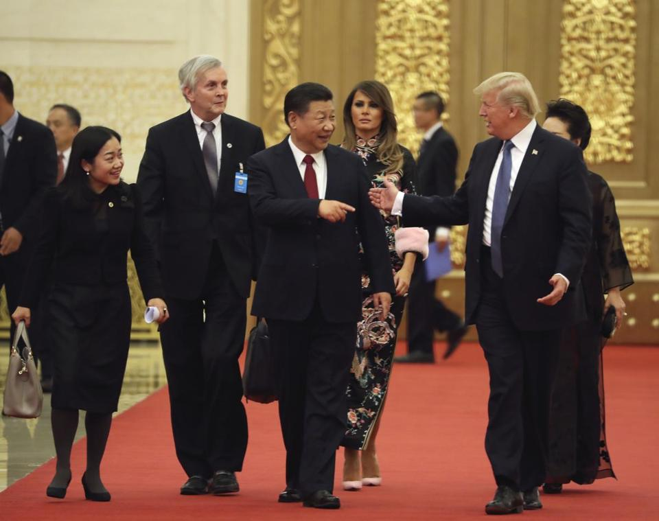 President Donald Trump (right) and Chinese President Xi Jinping (center) arrive at the Great Hall of the People.