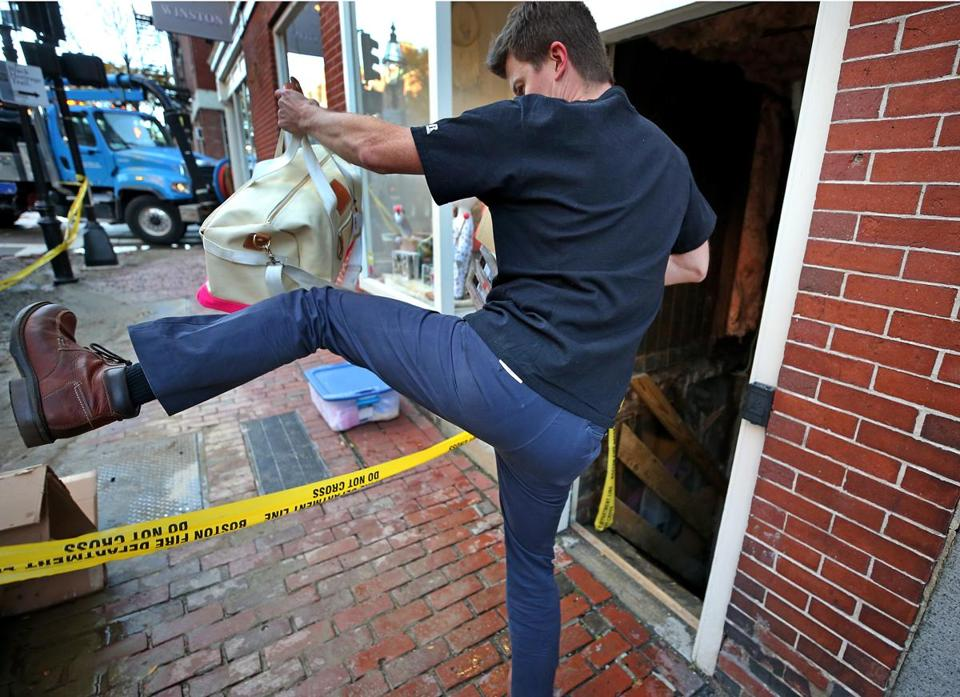 Tim Ayers helped remove  items from a flooded basement on Charles Street Friday.