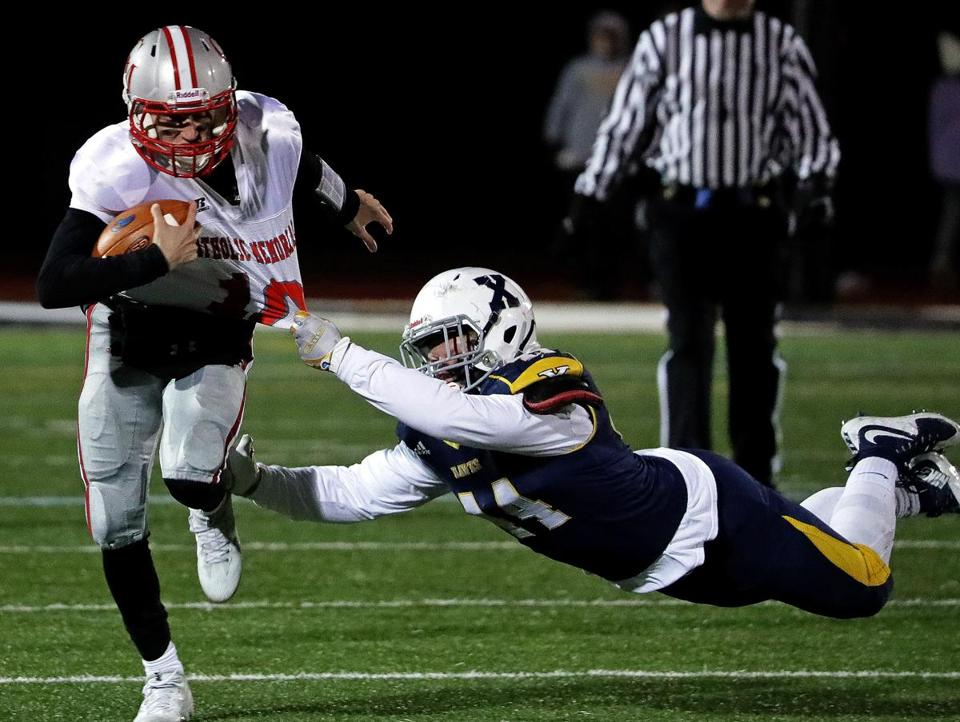 Westwood, MA - 11/10/2017 - Xaverian 's Nazio Defreitas (14) makes a diving tackle on CM quarterback Nick Goffredo (10) during the first quarter. Xaverian vs. Catholic Memorial in Division 1 South football semifinal.- (Barry Chin/Globe Staff), Section: Sports, Reporter: Owen Pence Topic: 11schxaverian, LOID: 8.4.12170797.