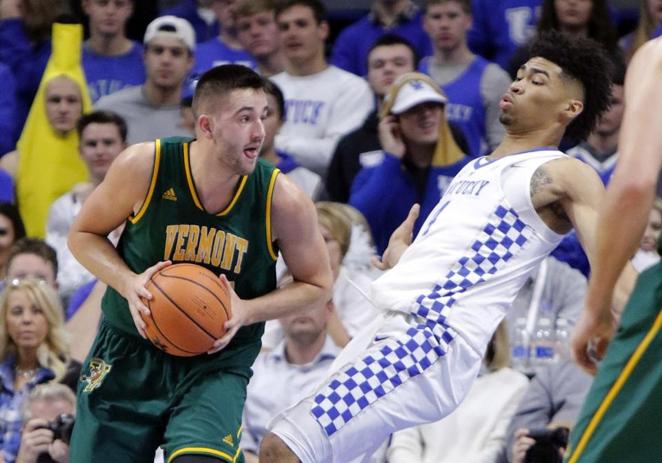 Vermont's Drew Urquhart, left, commits a charging foul against Kentucky's Nick Richards during the first half of an NCAA college basketball game, Sunday, Nov. 12, 2017, in Lexington, Ky. (AP Photo/James Crisp)
