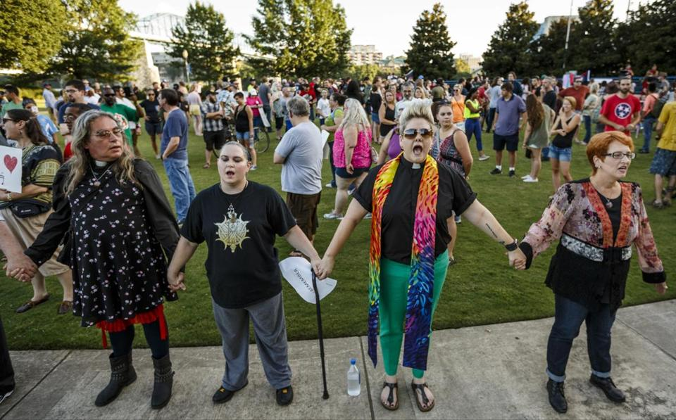 Volunteers form a line in front of demonstrators during a rally in Coolidge Park on Thursday, Aug. 17, 2017, in Chattanooga, Tenn. Organizers said that the purpose of the demonstration, held in response to Saturday's rally by white nationalists in Charlottesville, Va., was to declare resistance against Nazism. (Doug Strickland/Chattanooga Times Free Press via AP)