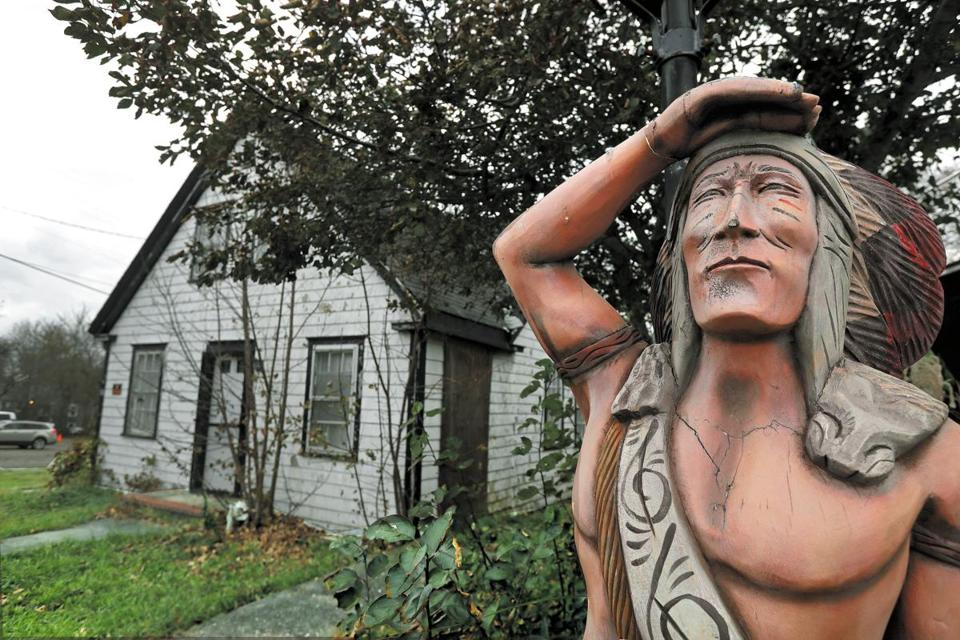 A carved wooden statue stands near a property in Sea Captains Row on Pleasant Street. A developer has proposed to tear down several 200-year-old neglected buildings for nine multifamily structures, pitting preservationists against some residents and business leaders.
