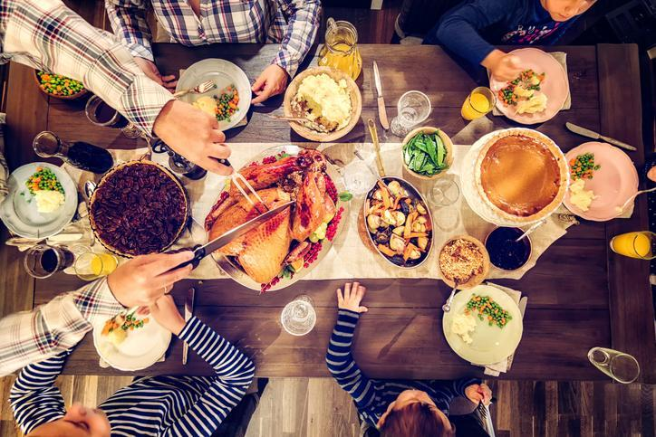 Family having traditional holiday dinner with stuffed turkey, mashed potatoes, cranberry sauce, vegetables pumpkin and pecan pie.
