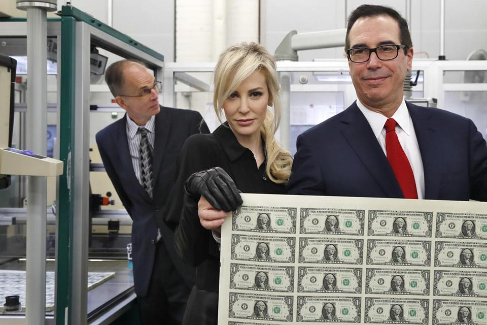 Treasury Secretary Steven Mnuchin, right, and his wife Louise Linton, held up a sheet of new $1 bills.
