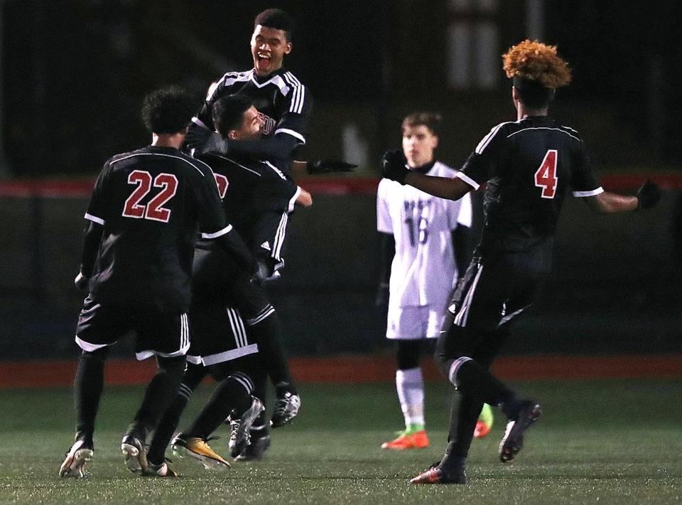 Brockton, MA: 11-14-17: Brockton's Jaylon DaRosa leaps into the arms of teammate Esteven Gomes after DaRosa put his team ahead 1-0 with a first half goal. St. John's Prep took on Brockton in the Division One Boy's State Soccer Semi-Finals at Brockton High School. (Jim Davis/Globe Staff)