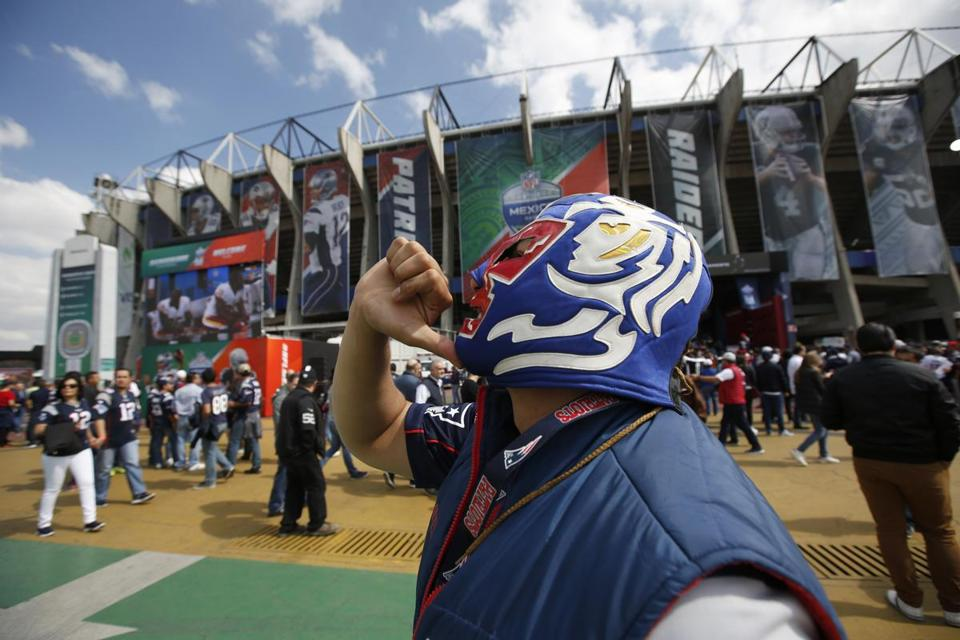 A Patriots fan poses with his wrestler's mask in front of Estadio Azteca.