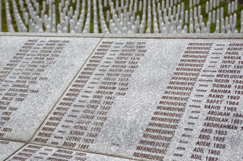 In this Thursday, Nov. 16, 2017, photo, names of the victims are carved on a monument at the memorial center of Potocari near Srebrenica, Bosnia. As a U.N court prepares to hand down its verdict in the case against Ratko Mladic, the Bosnian Serb military leader during the Balkan country's 1992-5 war, the remains of numerous victims of genocide and war crimes of which he stands accused still await identification.(AP Photo/Amel Emric)