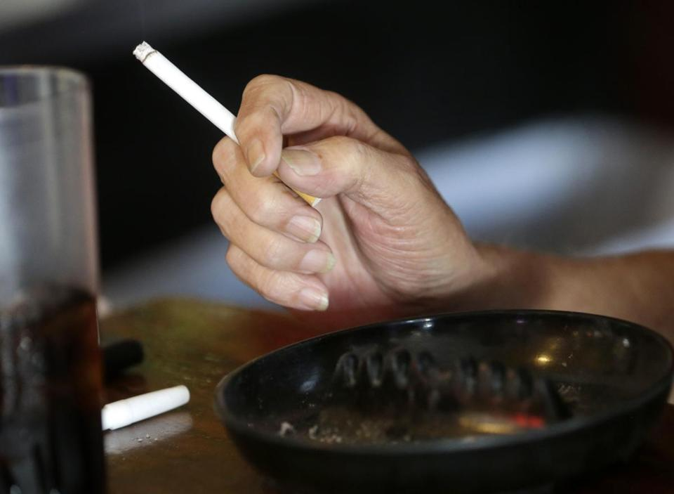 FILE - In this April 21, 2015, file photo, a patron smokes a cigarette inside a bar in New Orleans hours before a smoking ban takes effect in bars, gambling halls and many other public places such as hotels, workplaces, private clubs and stores. Cigarette smoking, over-eating and other unhealthy behaviors can be blamed for nearly half of U.S. cancer deaths each year, according to a new American Cancer Society study released Tuesday, Nov. 21, 2017. (AP Photo/Gerald Herbert, File)