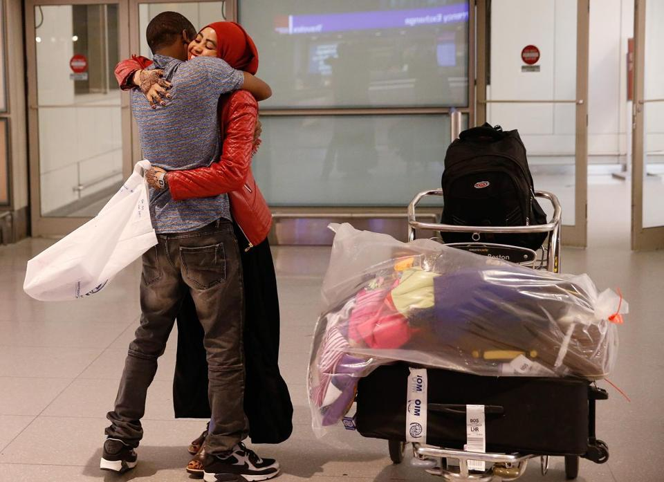 Hassan Abdullahi of Springfield (left) embraced his wife, Barlin Yarow, as she arrived from Kenya at Logan Airport.
