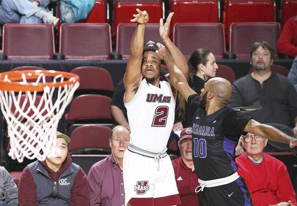 UMass's Luwane Pipkins throws a 3-pointer from the corner over Niagara's Kahlil Dukes in the second half of an NCAA college basketball game, Sunday, Nov. 19, 2017 in Amherst, Mass. (J. Anthony Roberts/The Republican via AP)
