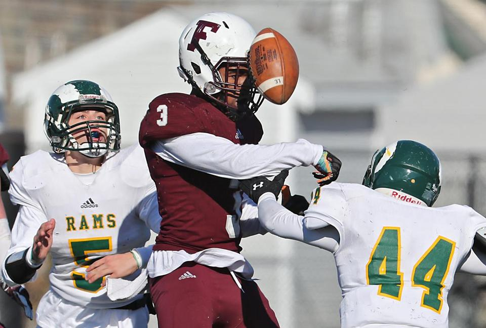 Ski Gaston of Lynn English knocked the ball loose from Lynn Classical's Manny Guerrero (44) as Marcus Tucker looked on.