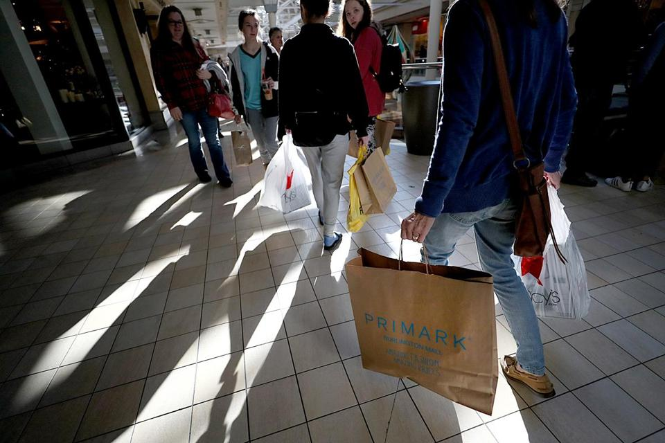 A National Retail Federation survey found that 174 million Americans made purchases over the five-day weekend. Above: Shoppers moved in and out of Primark at the Burlington Mall on Friday.
