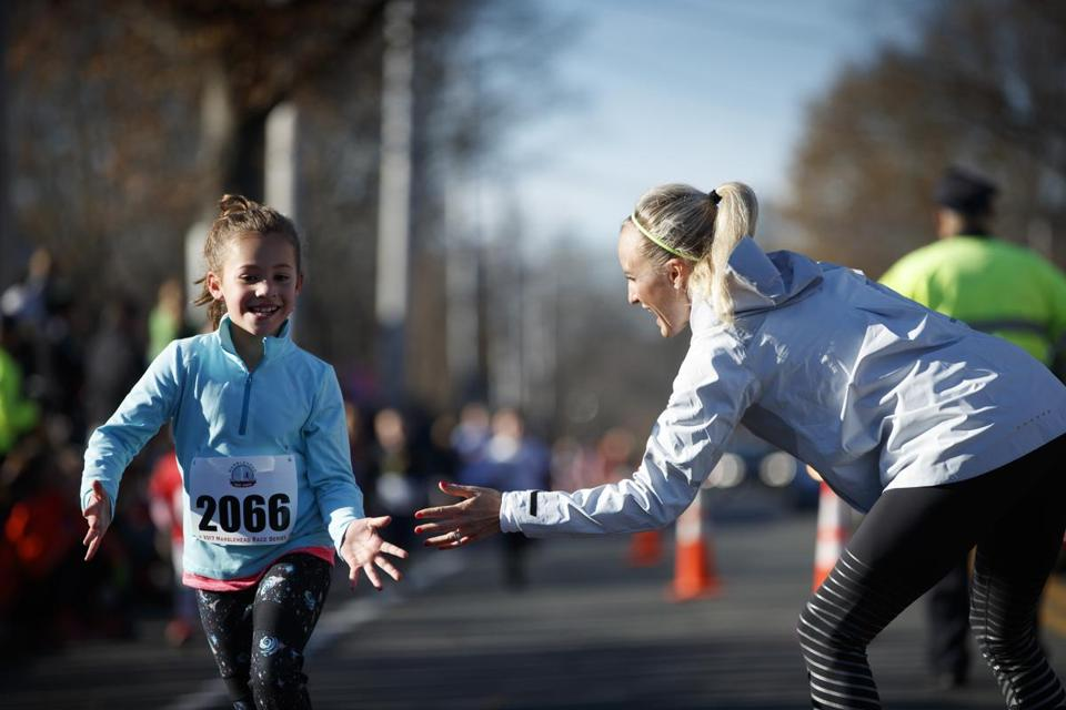 New York City Marathon winner Shalane Flanagan greeted Elise Rowland, 8, of Marblehead, at the end of a 1-mile kids' run Saturday in her hometown of Marblehead.