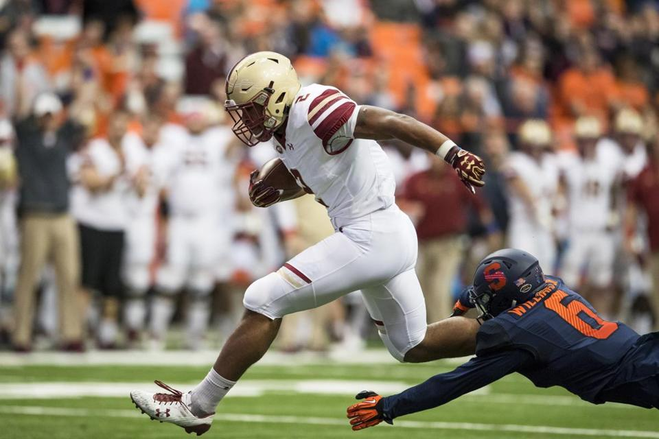 SYRACUSE, NY - NOVEMBER 25: AJ Dillon #2 of the Boston College Eagles hurdles to avoid a tackle by Rodney Williams #6 of the Syracuse Orange on a touchdown carry during the first quarter at the Carrier Dome on November 25, 2017 in Syracuse, New York. (Photo by Brett Carlsen/Getty Images)