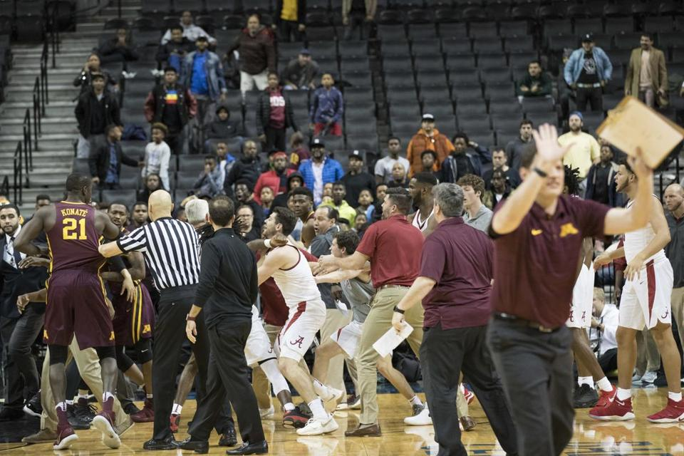 A member of the Minnesota caching staff, right, gestures for his players to stay on the bench after a fight during the second half of an NCAA college basketball game between Minnesota and Alabama, Saturday, Nov. 25, 2017, in New York. Minnesota won 89-84.(AP Photo/Mary Altaffer)