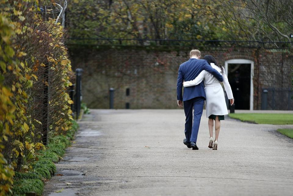 Britain's Prince Harry and Meghan Markle walked away after posing for the media in the grounds of Kensington Palace in London on Monday.