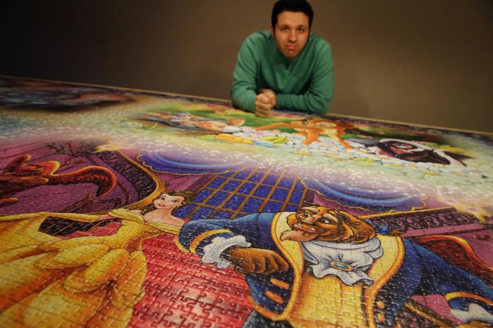Jack Brait posed for a portrait with his completed Ravensburger Puzzle at his home in Marshfield.