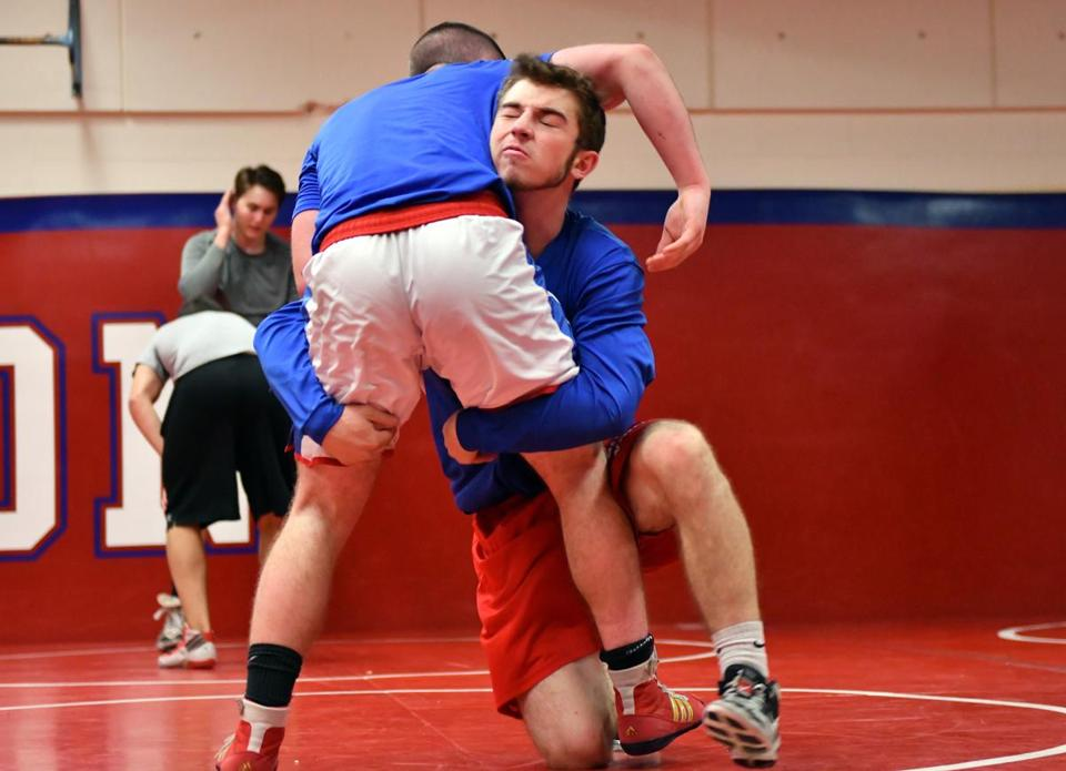 Burlington High senior wrestling captain Josh Lee, right a three-time state champion. exercises with Sean McGillivray during Practice at Burlington Higth School. Josh Reynolds for The Boston Globe (WeWk, petrini)