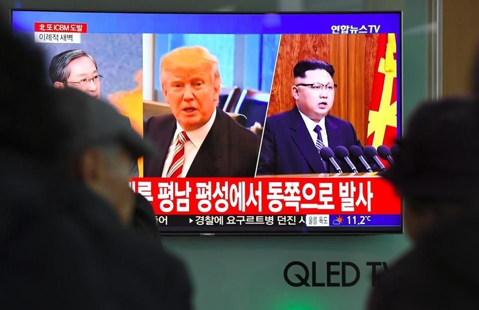 People watched a television news screen showing pictures of President Donald Trump and North Korean leader Kim Jong-Un at a railway station in Seoul on Wednesday.
