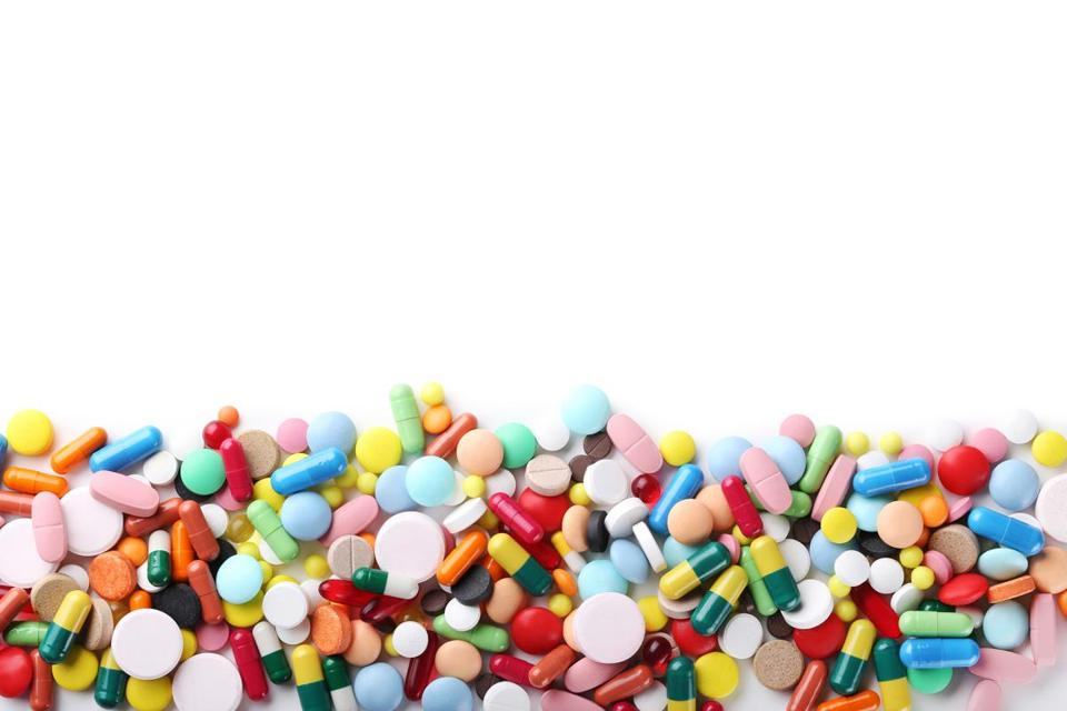 Different colorful pills on white background