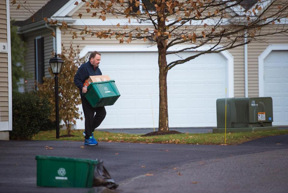 Len Zavalick took his neighbor's recycling and garbage to the curb for pick-up in Holliston.