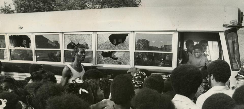 A crowd watches as a bus carrying students returns to Columbia Point with broken windows on Sept. 12, 1974, the first day of school under the new busing system put in place to desegregate Boston Public Schools.