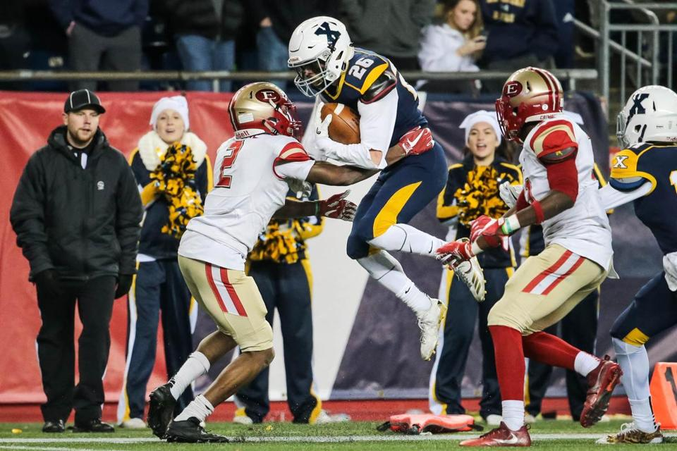 Jason Maitre (2) has his hands full trying to stop Xaverian's Cooper DeVeau on Saturday night.