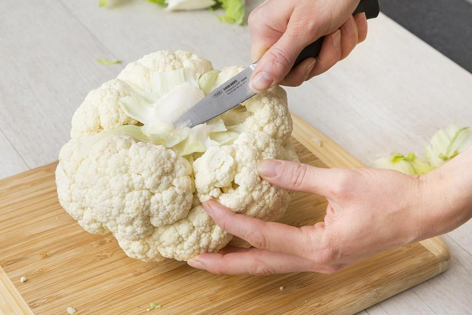 "When you plan to cook and present the cauliflower whole, you want it to stay intact. So rather than cutting into the head deeply to remove the whole core, I do what I call ""shallow-coring."" With the base of the cauliflower facing up or to one side, hold a paring knife at a wide angle and cut only about 1 inch deep. Work the knife in a circle to remove the stem and a shallow, cone-shaped piece of the core."