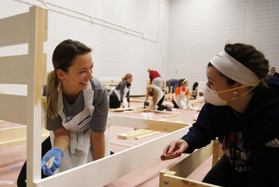 Salem, MA -- 12/04/2017 - Salem State Sophomore Gabby Cerro (cq) (L) laughs with Salem State Junior Chloe Manousos as they work to build beds for children who don't have one. Salem State students and alumni gathered to build 50 beds in a four hour period as part of the Build-a-Bed challenge. Thousands of children in Massachusetts sleep on couches, the floor, or share beds with their parents because their family can't afford a bed. (Jessica Rinaldi/Globe Staff) Topic: 05beds Reporter: