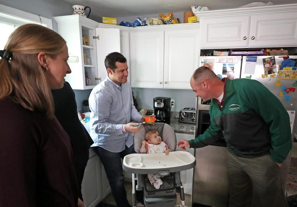 Keene, N.H., police officer Steve Tenney (right) plays with Sloan St. James, the baby who received part of his liver. At left in the child's Bourne kitchen are her mother, Sarah, and father, Chris.