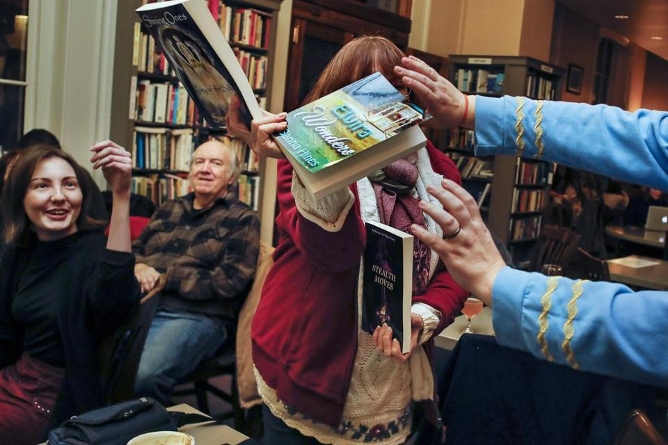 "Author Sanna Hines of Maine, center, gets help holding up her books to get feedback on the cover art at the Book and Bar ""Writers Night Out'' event in Portsmouth, NH Monday, Dec. 4, 2017. CREDIT: Cheryl Senter for The Boston Globe"