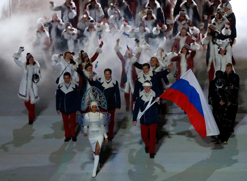 "(FILES) This file photo taken on February 07, 2014 shows Russian model Irina Shayk leading Russia's flag bearer, bobsledder Alexander Zubkov, and the delegation during the Opening Ceremony of the Sochi Winter Olympics at the Fisht Olympic Stadium in Sochi. Russia were banned from the 2018 Olympics on December 5, 2017 over state-sponsored doping but the International Olympic Committee said Russian competitors would be able to compete ""under strict conditions"". / AFP PHOTO / ADRIAN DENNISADRIAN DENNIS/AFP/Getty Images"