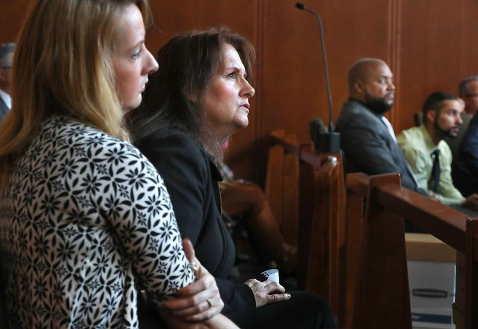 Joshua Messier's mother, Lisa Brown (left) and sister, Danielle looked at an image projected on a screen in the courtroom, as two of the three guards on trial, Derek Howard (left rear) and John Raposo looked on.