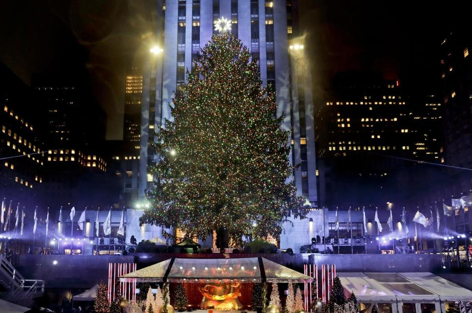 FILE - This photo from Wednesday Nov. 30, 2016 shows the Rockefeller Center Christmas tree as it stands lit during the 84th annual Rockefeller Center Christmas tree lighting ceremony in New York. After it was taken down the 94-foot Norway spruce was milled into lumber and trucked 50 miles north again to Newburgh,N.Y., where Habitat for Humanity volunteers recently used the planks to fix up two brick-front homes. (AP Photo/Julie Jacobson, File)