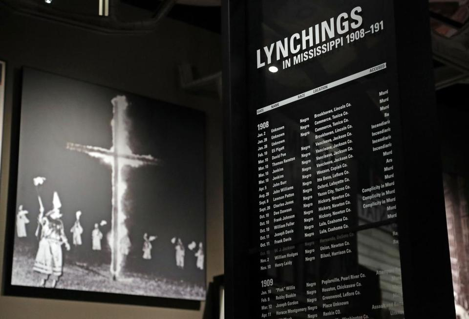 In this Nov. 10, 2017 image, a monolith listing the names, dates and rationale for the lynching of African-American residents rests in the foreground of a photograph of a burning Ku Klux Klan cross on display in the Mississippi Civil Rights Museum in Jackson, Miss. The monolith is one of several that line this gallery with the documented lynchings. Room has been left for updating as needed. This facility is adjacent to the newly built Museum of Mississippi History, that documents the state's rich history and the diversity of its people. Work crews and archivists are putting the final touches on the two museums set to open Dec. 9. (AP Photo/Rogelio V. Solis)