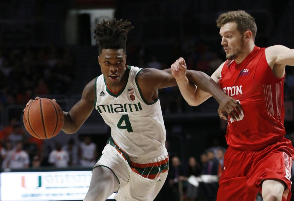 Miami guard Lonnie Walker IV (4) drives past Boston University guard Will Goff during the first half of an NCAA college basketball game, Tuesday, Dec. 5, 2017, in Coral Gables, Fla. (AP Photo/Wilfredo Lee)