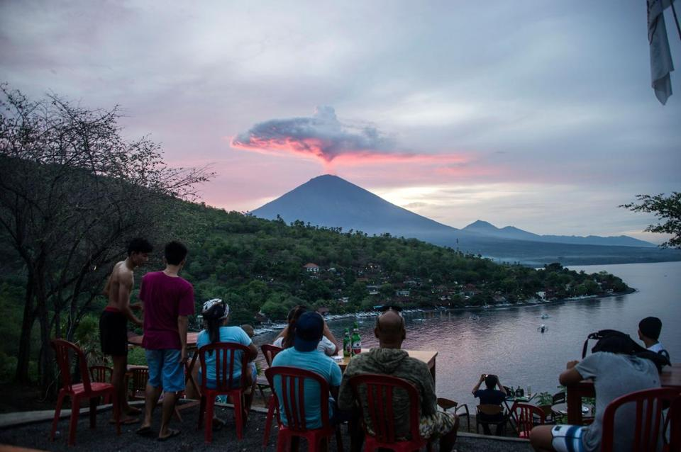 Tourists gather to watch Mount Agung at Amed beach in Karangasem on Indonesia's resort island of Bali on November 30, 2017. Thousands of foreign tourists were expected to leave Bali by plane on November 30 following a nearly three-day airport shutdown sparked by a rumbling volcano on the Indonesian holiday island. / AFP PHOTO / JUNI KRISWANTOJUNI KRISWANTO/AFP/Getty Images