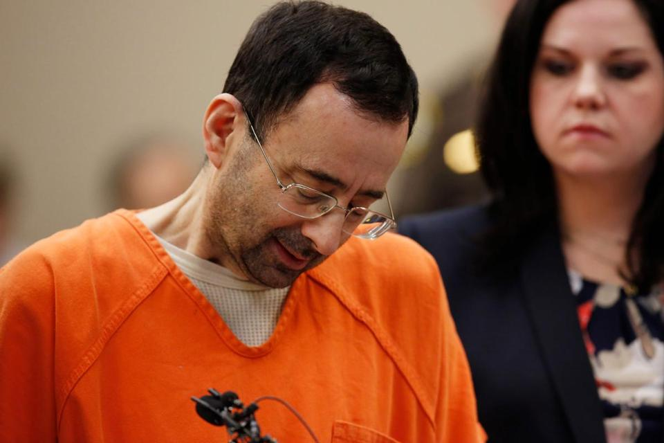 (FILES) This file photo taken on November 22, 2017 shows former Michigan State University and USA Gymnastics doctor Larry Nassar (L) as he reacts to defense attorney Shannon Smith (R) reading the charges he pled to in Ingham County Circuit Court in Lansing, Michigan. Larry Nassar is scheduled to be sentenced in federal court in Michigan on December 7, 2017 after pleading guilty to child pornography charges.He has also pleaded guilty to 10 counts of sexual assault in two other cases in Michigan, admitting that he abused young athletes under the guise of offering medical treatment. / AFP PHOTO / JEFF KOWALSKYJEFF KOWALSKY/AFP/Getty Images