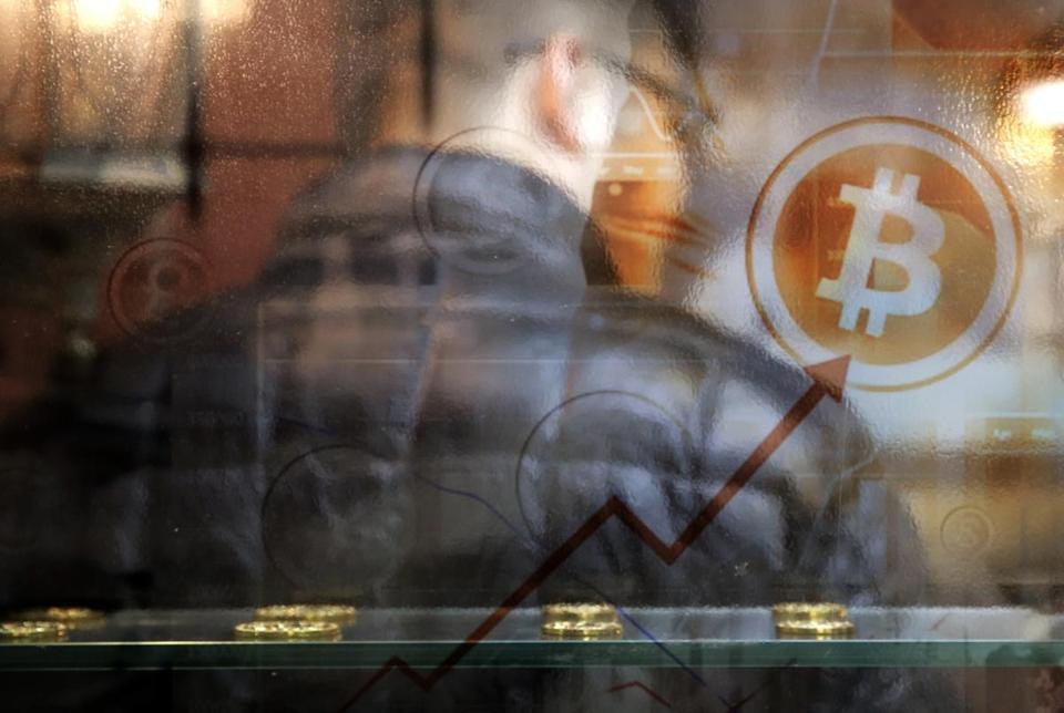 A man uses a Bitcoin ATM in Hong Kong, Friday, Dec. 8, 2017. Bitcoin is the world's most popular virtual currency. Such currencies are not tied to a bank or government and allow users to spend money anonymously. They are basically lines of computer code that are digitally signed each time they are traded. (AP Photo/Kin Cheung)