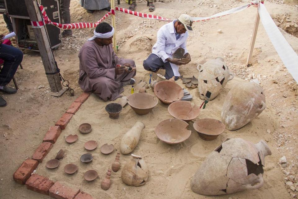 "Egyptian excavation workers restore pottery near a new found in a tomb in Draa Abul Naga necropolis on Luxor's West Bank known as ""KAMPP 161"" during an announcement for the Egyptian Ministry of antiquities about new discoveries in Luxor, Egypt, Saturday, Dec. 9, 2017. Egypt's Antiquities Ministry says archaeologists have discovered two ancient tombs in the southern city of Luxor. The ministry said Saturday that one tomb has five entrances leading to a rectangular hall, and contains painted wooden funerary masks, clay vessels and a mummy wrapped in linen. (AP Photo/Hamada Elrasam)"