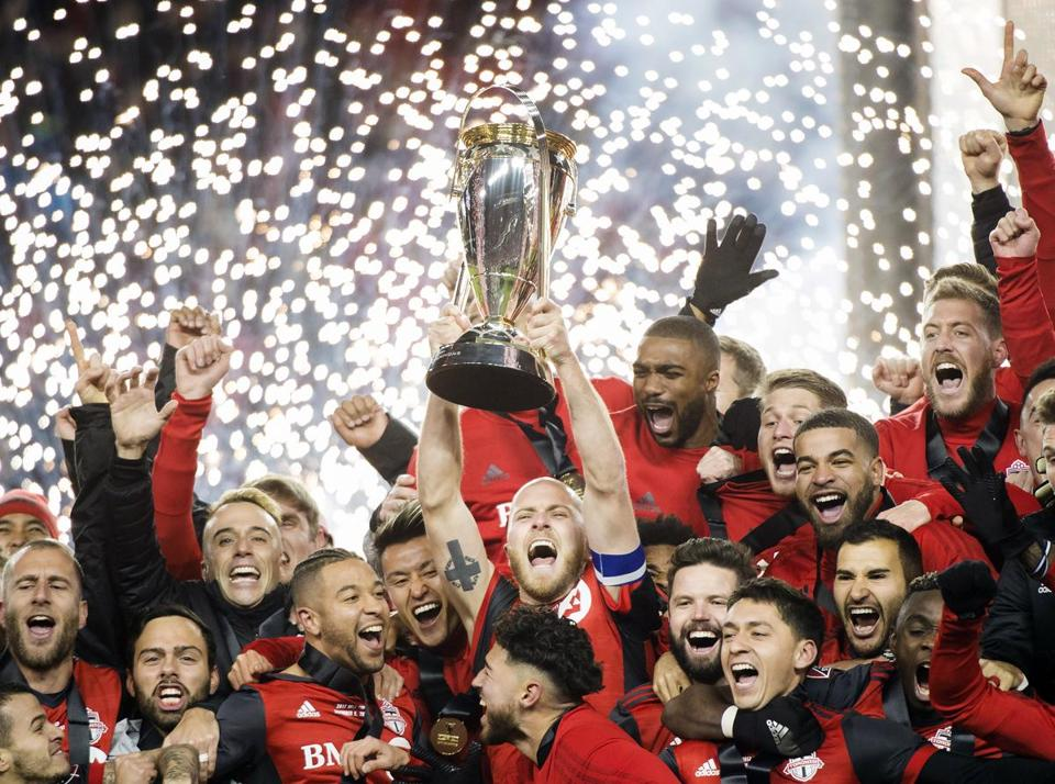 Toronto FC captain Michael Bradley hoists the trophy as the team celebrates its win over the Seattle Sounders in the MLS Cup final in Toronto, Saturday, Dec. 9, 2017. (Nathan Denette/The Canadian Press via AP)