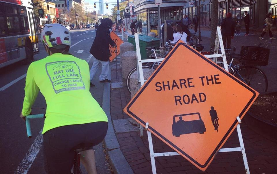 "The can't-miss neon yellow T-shirt and backpack cover double as moving road signs. Printed on the back, in bold type with reflective lettering, is the warning:""[Cyclists] May Use Full Lane, Change Lanes to Pass."""