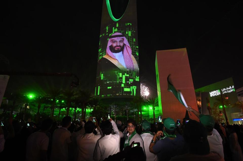 People watch a projection depicting a portrait of Crown Prince Mohammed bin Salman during an event in the capital Riyadh on late September 23, 2017 commemorating the anniversary of the founding of the kingdom. The national day celebration coincides with a crucial time for Saudi Arabia, which is in a battle for regional influence with arch-rival Iran, bogged down in a controversial military intervention in neighbouring Yemen and at loggerheads with fellow US Gulf ally Qatar. / AFP PHOTO/AFP/Getty Images