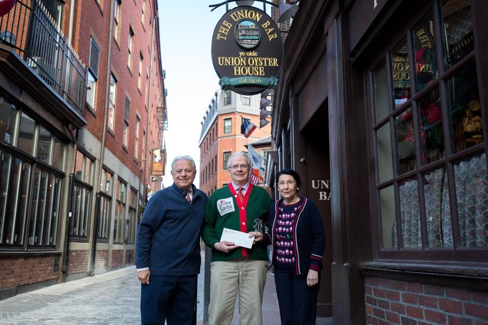 The owners of the Union Oyster House, Joe and Mary Ann Milano, flanked executive director of Globe Santa Bill Connolly outside the venerable Boston restaurant. Union Oyster House gave $5,000, part of a longstanding tradition.