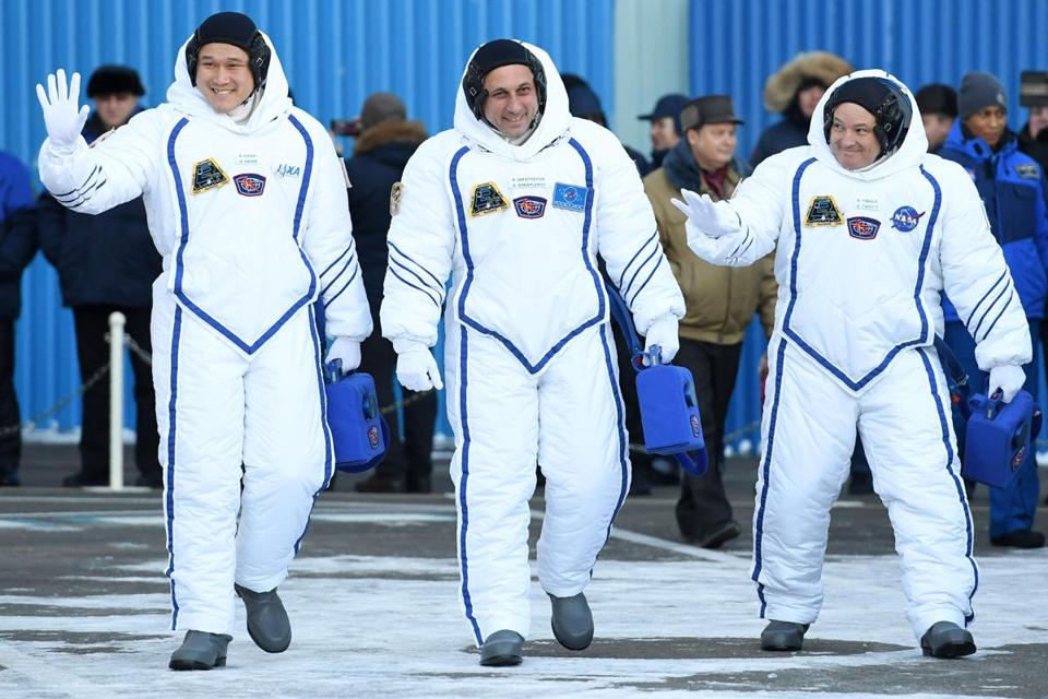 The newest International Space Station residents (from left) Norishige Kanai, Anton Shkaplerov, and Scott Tingle waved during a send-off ceremony in Kazakhstan.