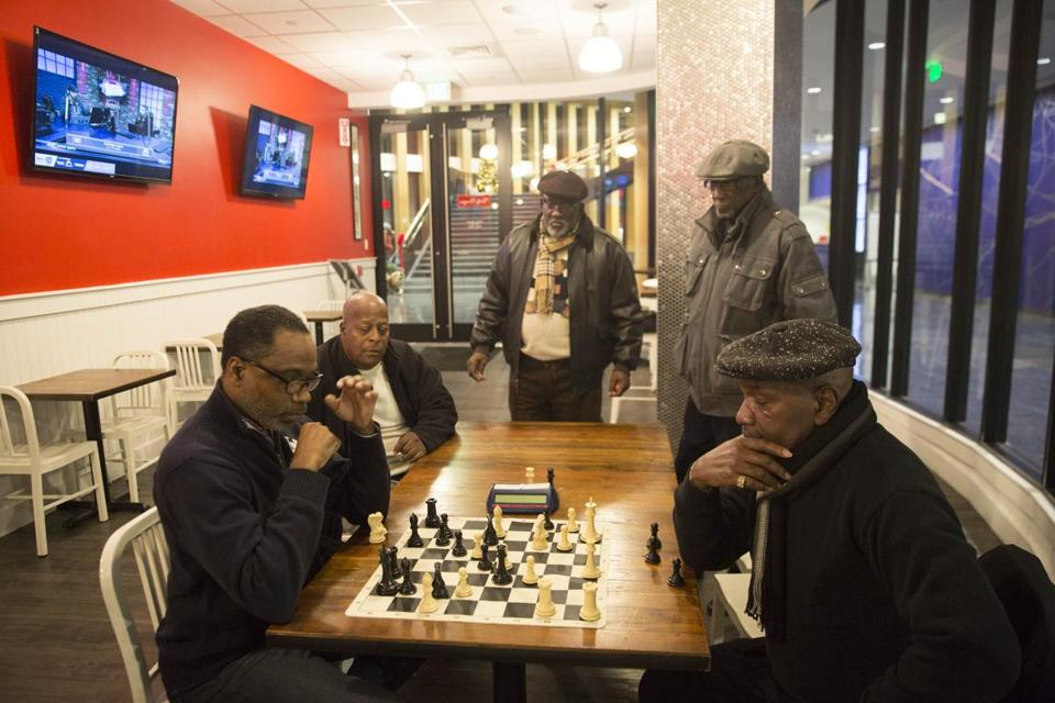 Men gathered to play chess in a nearly empty Tasty Burger, which will close soon, in Dudley Square.  A new restaurant is planned for the site.