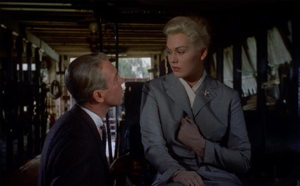 "For ""Vertigo,"" designer Edith Head dressed Kim Novak (with costar Jimmy Stewart) in a gray suit to play the blonde Madeleine."