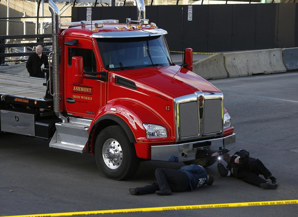 Boston Police inspected the underside of a truck involved in a fatal pedestrian accident on Herald Street at Washington on Wednesday.