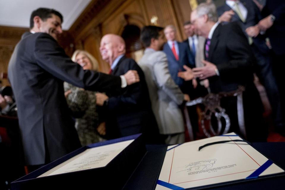 The signatures of Speaker of the House Paul Ryan, R-Wis., and Senate Finance Committee Chairman Orrin Hatch, R-Utah, foreground can be seen as Ryan, left, and House Ways and Means Committee Chairman Kevin Brady, R-Texas, second from left, congratulate each other after signing the final version of the GOP tax bill during an enrollment ceremony at the Capitol in Washington, Thursday, Dec. 21, 2017. (AP Photo/Andrew Harnik)